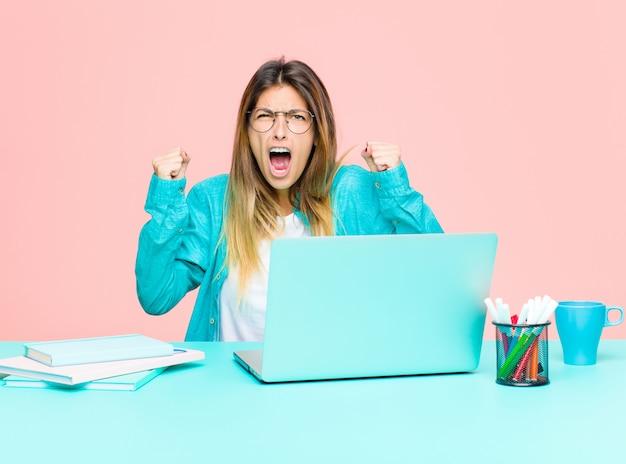 Mujer bonita joven que trabaja con una computadora portátil gritando agresivamente con una expresión enojada o con los puños cerrados para celebrar el éxito