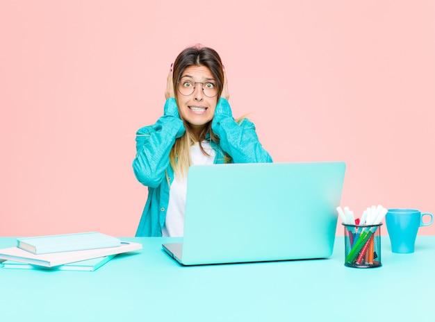 Mujer bonita joven que trabaja con una computadora portátil que parece desagradablemente sorprendida, asustada o preocupada, con la boca abierta y cubriendo ambas orejas con las manos