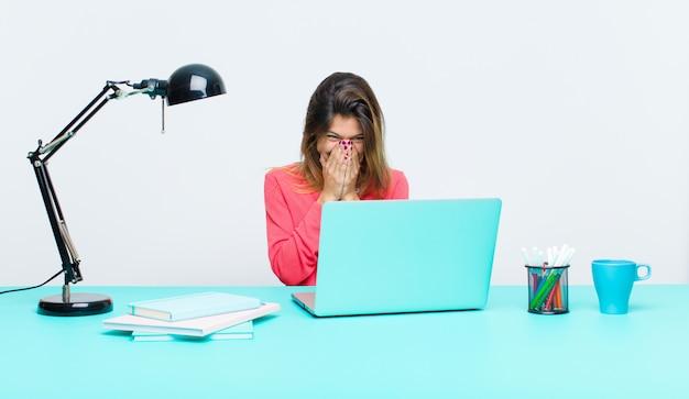 Mujer bonita joven que trabaja con una computadora portátil que parece feliz, alegre, afortunada y sorprendida cubriendo la boca con ambas manos
