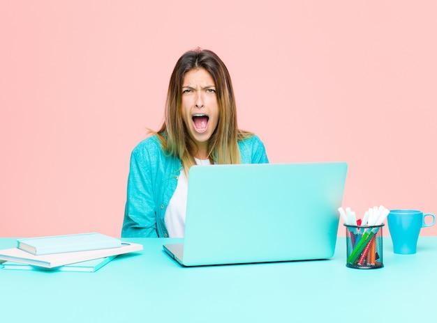 Mujer bonita joven que trabaja con una computadora portátil que parece sorprendida, enojada, molesta o decepcionada, con la boca abierta y furiosa