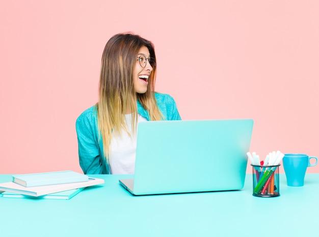 Mujer bonita joven que trabaja con una computadora portátil que se siente feliz