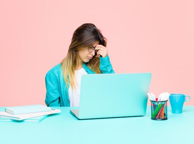 Mujer bonita joven que trabaja con una computadora portátil sintiéndose estresada, infeliz y frustrada, tocando la frente y sufriendo migraña de dolor de cabeza intenso