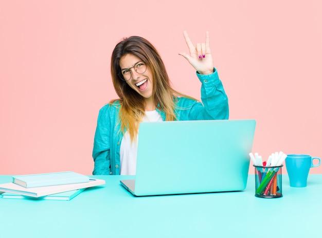 Mujer bonita joven que trabaja con una computadora portátil sintiéndose feliz, divertida, segura, positiva y rebelde, haciendo un cartel de rock o heavy metal con la mano