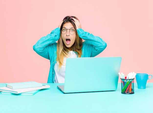 Mujer bonita joven que trabaja con una computadora portátil sintiéndose horrorizada y conmocionada, levantando las manos a la cabeza y entrando en pánico ante un error