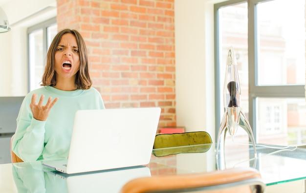 Mujer bonita joven que trabaja, que parece enojada, molesta y frustrada gritando wtf o qué pasa contigo