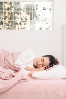 Mujer bonita joven relajada durmiendo en la cama con teléfono móvil de pantalla en blanco