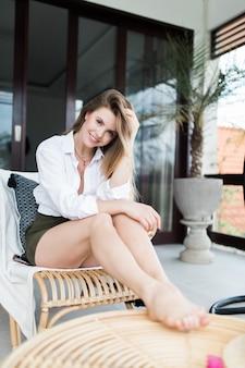 Mujer bonita joven relajándose en la hermosa terraza en el columpio