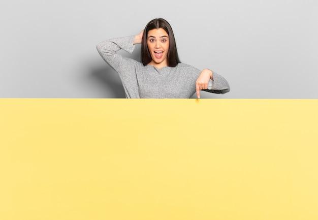 Mujer bonita joven riendo, luciendo feliz, positiva y sorprendida, dándose cuenta de una gran idea apuntando al espacio lateral de la copia.