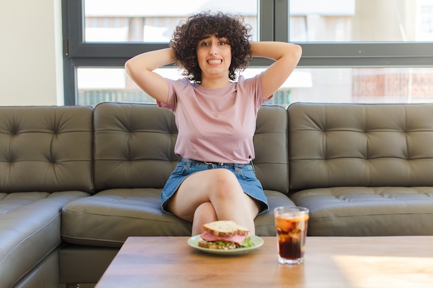 Mujer bonita joven con un sándwich sentado en un sofá en casa