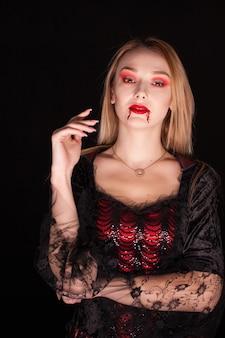 Mujer bonita joven con sangre en los labios vestida como un vampiro para halloween sobre fondo negro.