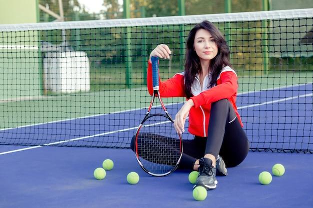 Mujer bonita joven sentada apoyado en la red de tenis, descansando relajante después del entrenamiento. retrato de deportista en tenis azul cour. vida saludable. copie el espacio.