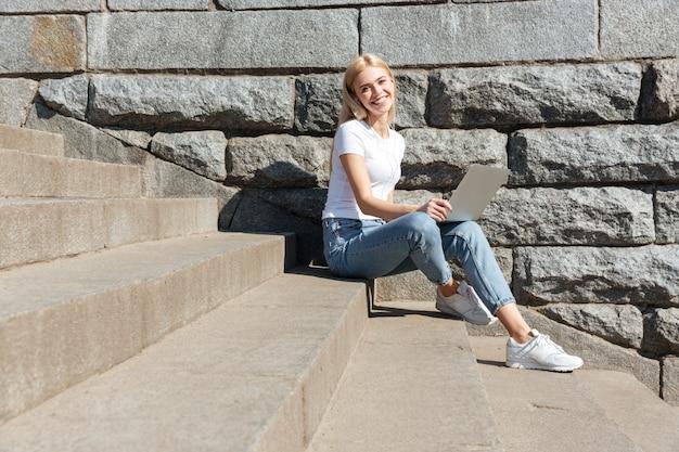 Mujer bonita joven sentada en las escaleras con ordenador portátil