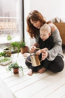 Mujer bonita joven sentada en el piso con su pequeño hijo guapo sosteniendo regadera en manos con plantas verdes alrededor de ventana grande