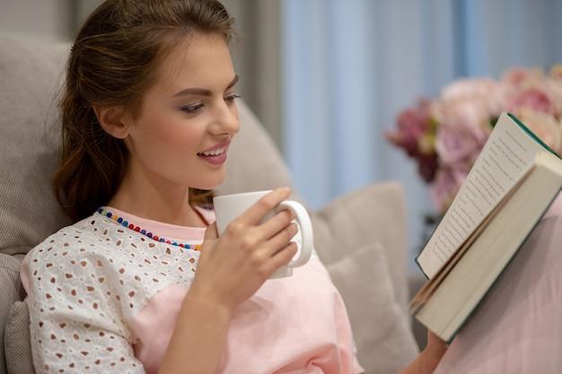 Mujer bonita joven sentada en el sofá tomando café y leyendo un libro disfruta del descanso