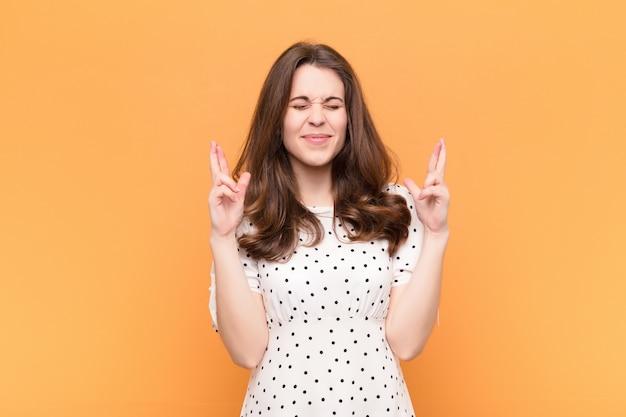 Mujer bonita joven sintiéndose nerviosa y esperanzada, cruzando los dedos, rezando y esperando buena suerte sobre la pared naranja