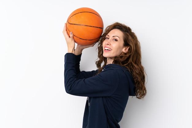 Mujer bonita joven sobre aislado con pelota de baloncesto