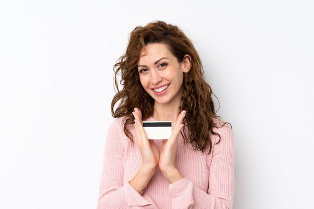 Mujer bonita joven sobre aislado sosteniendo una tarjeta de crédito