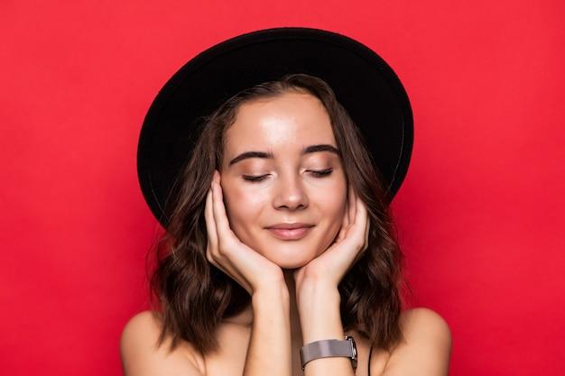 Mujer bonita joven con sombrero de ala ancha aislado sobre rojo