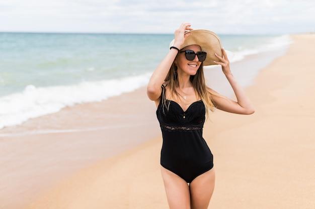 Mujer bonita joven con sombrero en la playa cerca del mar
