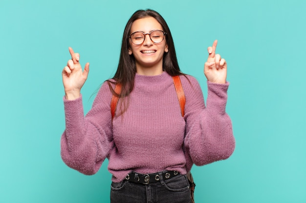 Mujer bonita joven sonriendo y cruzando ansiosamente ambos dedos, sintiéndose preocupada y deseando o esperando buena suerte. concepto de estudiante