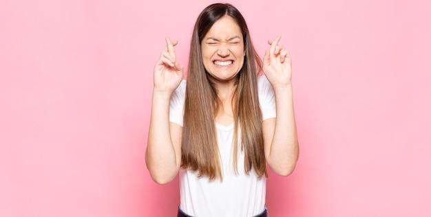 Mujer bonita joven sonriendo y cruzando ansiosamente ambos dedos, sintiéndose preocupada y deseando o esperando buena suerte