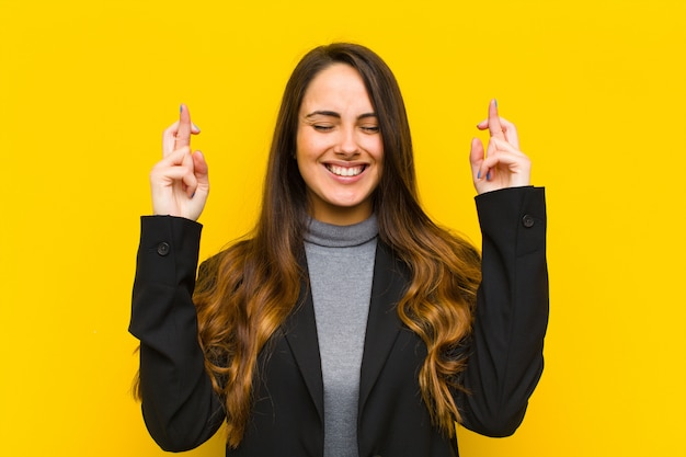 Mujer bonita joven sonriendo y cruzando ansiosamente ambos dedos, sintiéndose preocupada