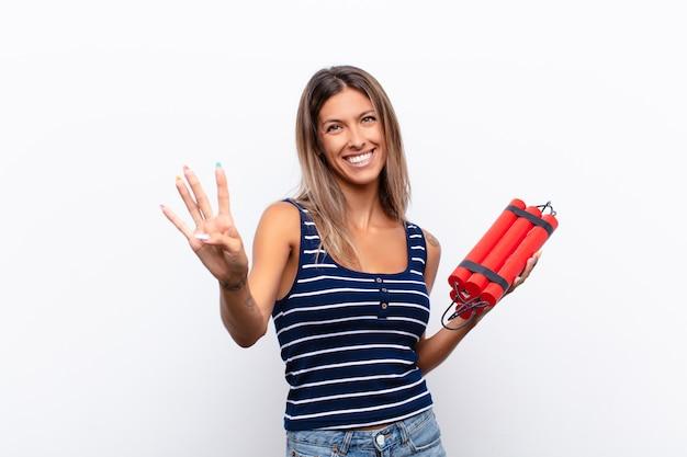 Mujer bonita joven sonriendo y mirando amigable, mostrando el número cuatro o cuarto con la mano hacia adelante, contando con una bomba de dinamita