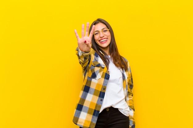 Mujer bonita joven sonriendo y mirando amigable, mostrando el número cuatro o cuarto con la mano hacia adelante, contando contra la pared naranja