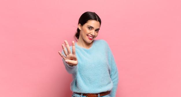 Mujer bonita joven sonriendo y mirando amistosamente, mostrando el número cuatro o cuarto con la mano hacia adelante, contando hacia atrás
