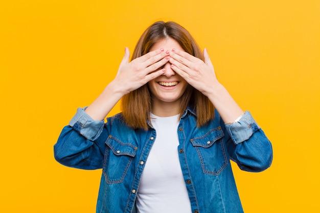 Mujer bonita joven sonriendo y sintiéndose feliz, cubriendo los ojos con ambas manos y esperando una sorpresa increíble contra la pared amarilla
