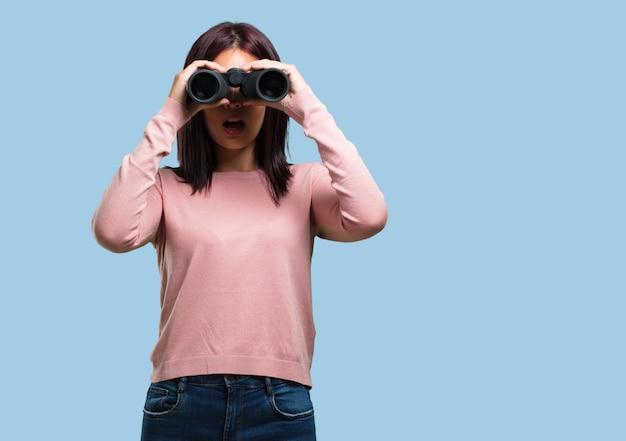 Mujer bonita joven sorprendida y sorprendida, mirando con binoculares en la distancia