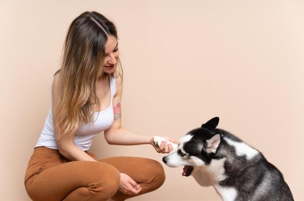 Mujer bonita joven con su perro husky sentado en el suelo en el interior