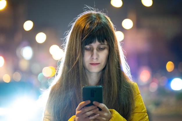 Mujer bonita joven con su teléfono móvil de pie en las calles de la ciudad por la noche al aire libre.