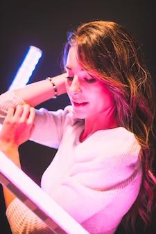 Mujer bonita joven en suéter blanco mirando a la cámara con mirada seductora con luces led rosas y azules