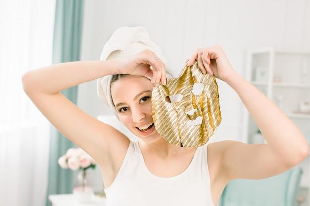 Mujer bonita joven en la toalla blanca después del baño que sostiene la máscara facial de oro del papel. mujer que consigue la máscara facial de oro.