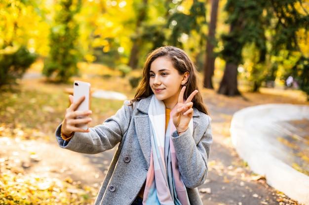 Mujer bonita joven toma el teléfono por teléfono en el parque otoño