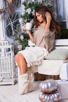 Mujer bonita joven tomando café con árbol de navidad