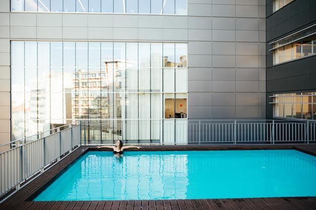 Mujer bonita joven en traje de baño negro se relaja en el borde de la piscina