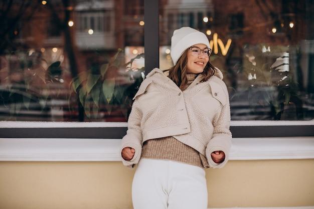 Mujer bonita joven en traje beige caminando por la calle en invierno