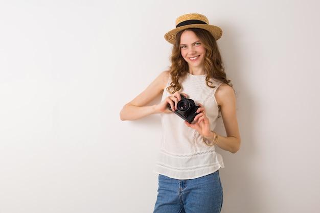 Mujer bonita joven en traje de estilo de vacaciones de verano con cámara de fotos vintage en blanco