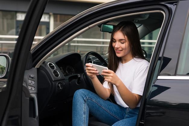 Mujer bonita joven usa el teléfono mientras está sentada en su auto nuevo