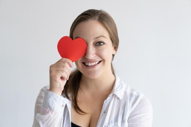 Mujer bonita juguetona que sostiene el corazón de papel delante de su ojo