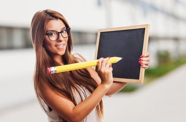 Mujer bonita con un lápiz grande