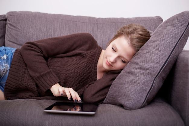 Mujer bonita con laptop en sofá