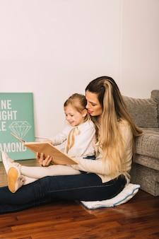 Mujer bonita leyendo el libro con la hija en el piso