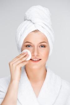 Mujer bonita en maquillaje de albornoz con esponja