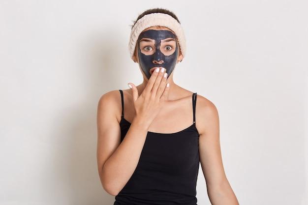 Mujer bonita con máscara facial de arcilla negra, niña sorprendida con banda para el cabello en la cabeza