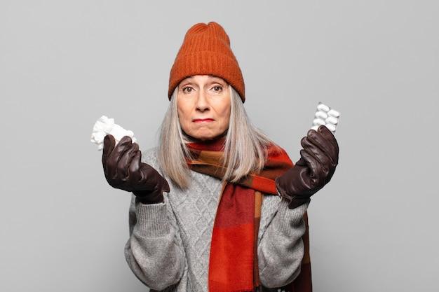 Mujer bonita mayor con una tableta de píldoras con ropa de invierno. concepto de gripe