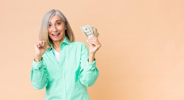 Mujer bonita de mediana edad con billetes de dólar contra la pared del espacio de copia