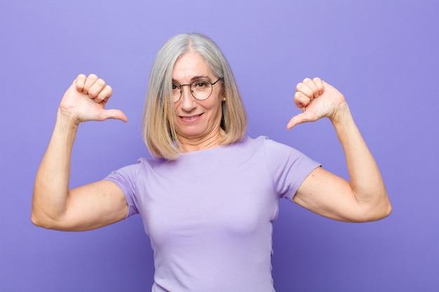 Mujer bonita de mediana edad o mayor que se siente orgullosa, arrogante y segura, que parece satisfecha y exitosa, apuntando a sí misma
